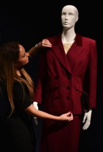 "A woman poses for a photograph with a burgundy wool twill suit, worn by Lady Margaret Thatcher when she left Downing Street after stepping down as Prime Minister in 1990, expected to realise 5,000 - 10,000 GBP (6,900-13,800 euros), during a photocall at Christie's auction house in central London on December 11, 2015, to promote their forthcoming auction ""Mrs Thatcher: Property from the Collection of the Right Honourable The Baroness Margaret Thatcher of Kesteven,"" which is set to take place on December 15. AFP PHOTO / BEN STANSALL / AFP / BEN STANSALL"