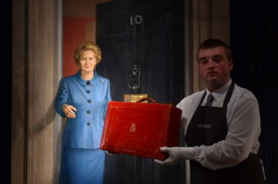 "An employee holds a red Prime Ministerial dispatch box used by former British Prime Minister Margaret Thatcher, and expected to realise £3,000 - 5,000 GPB (4,100 - 6,900 euros) at auction, in front of a painting entitled 'Lady Thatcher on the steps of No.10 Downing Street' by Britsih artist Michael Noakes, during a photocall at Christie's auction house in central London on December 11, 2015, to promote their forthcoming auction ""Mrs Thatcher: Property from the Collection of the Right Honourable The Baroness Margaret Thatcher of Kesteven,"" which is set to take place on December 15. The painting by Noakes will not form part of the sale, but is due to be auctioned separately. AFP PHOTO / BEN STANSALL RESTRICTED TO EDITORIAL USE, MANDATORY MENTION OF THE ARTIST UPON PUBLICATION, TO ILLUSTRATE THE EVENT AS SPECIFIED IN THE CAPTION / AFP / BEN STANSALL"