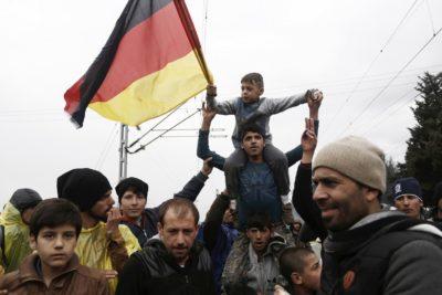 Migranti v Grčiji z Nemško zastavo jasno sporočajo, kam so namenjeni (foto: epa)