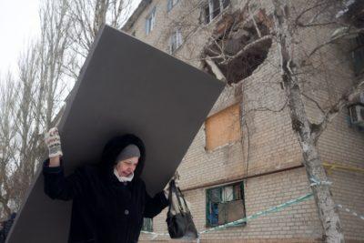 Prebivalka mesta Avdiivka nosi gradbeni material, s katerim bodo vsaj malo zakrpali luknje v njeni hiši. Slika je nastala 3. februarja 2017 po koncu silovitih spopadov v tem mestu. Foto: epa
